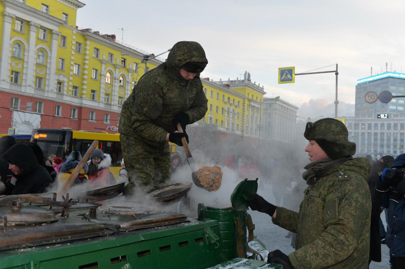 Due uomini distribuiscono piatti di grechka contenuti all'interno di un finto carro armato trasformato in una gigante stufa. Fonte: ufficio stampa