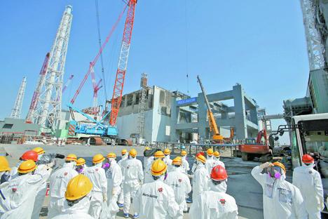 日本・福島:大災害から2年を迎える2013年3月6日、津波によって破壊された福島県の東京電力福島第1原子力発電所で、熔解した燃料棒を保管するために第4号機近くで土台を建設している現 場を、保護服をまといマスクを装用して、東京電力職員の案内で訪問する報道関係者たち。 =加藤一生/ロイター通信撮影