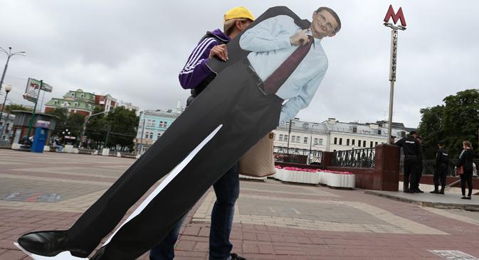 モスクワ市長選のニコライ・レヴィチェフ候補(公正ロシア)のイメージ画像をもつ選挙運動員。=タス通信撮影
