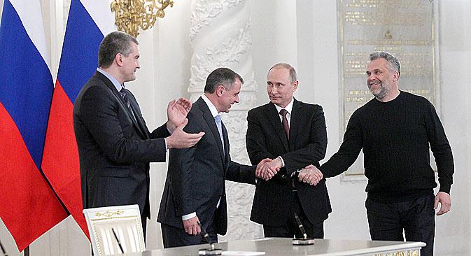 3月18日、プーチン大統領、セルゲイ·アクショーノフ・クリミア首相(左)、ウラジーミル・コンスタンティノフ・クリミア最高会議議長(左から二人目)、アレクセイ・チャルイ・セヴァストポリ特別市市長が、 クレムリンでのクリミア併合調印式の後、連邦議会議員の前に立つ=コンスタンチン・ザウラジン / ロシースカヤ・ガゼタ(ロシア新聞)