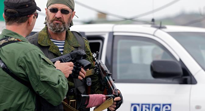 ウクライナ東部のニジニャ・クリンカ村で23日、親ロシア派がOSCEの車両を護衛。ウクライナ東部の停戦は、政府軍と親ロシア派によって守られている。今月初めからの停戦第1段階はくり返し破られていた。=AP通信