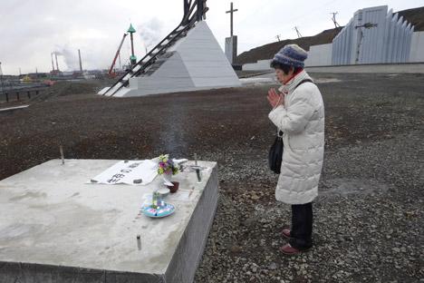 渡辺祥子さんが慰霊碑建立予定地で祈る。=マリア・レブローヴァ撮影