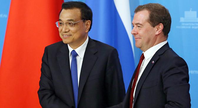 ロシアのメドベージェフ首相と訪露した中国の李克強首相(左)がモスクワでの会談後、最後の記者会見前に握手する。=AP通信