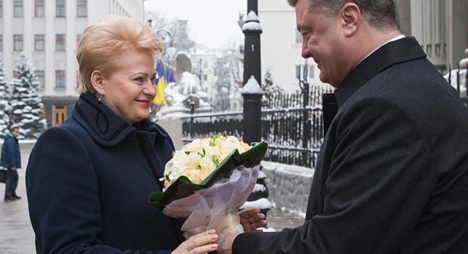 ウクライナのペトロ・ポロシェンコ大統領(右)が、リトアニアのダリア・グリバウスカイテ大統領を歓迎する。11月24日、ウクライナ、キエフ。=AP通信