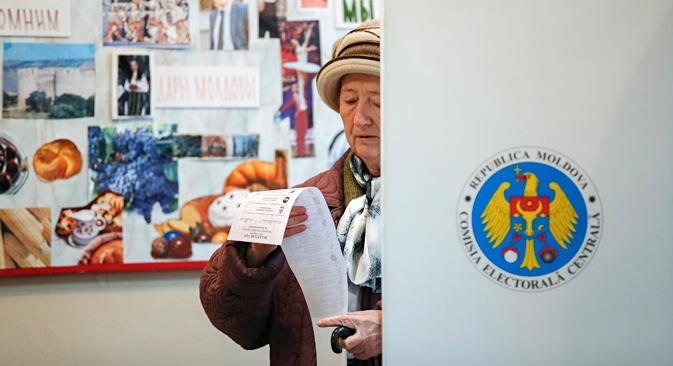 11月30日、モルドバ共和国の首都キシナウ(キシニョフ)。同国の議会選挙に際し、女性が投票所で自分の投票用紙を読んでいる。=ロイター通信