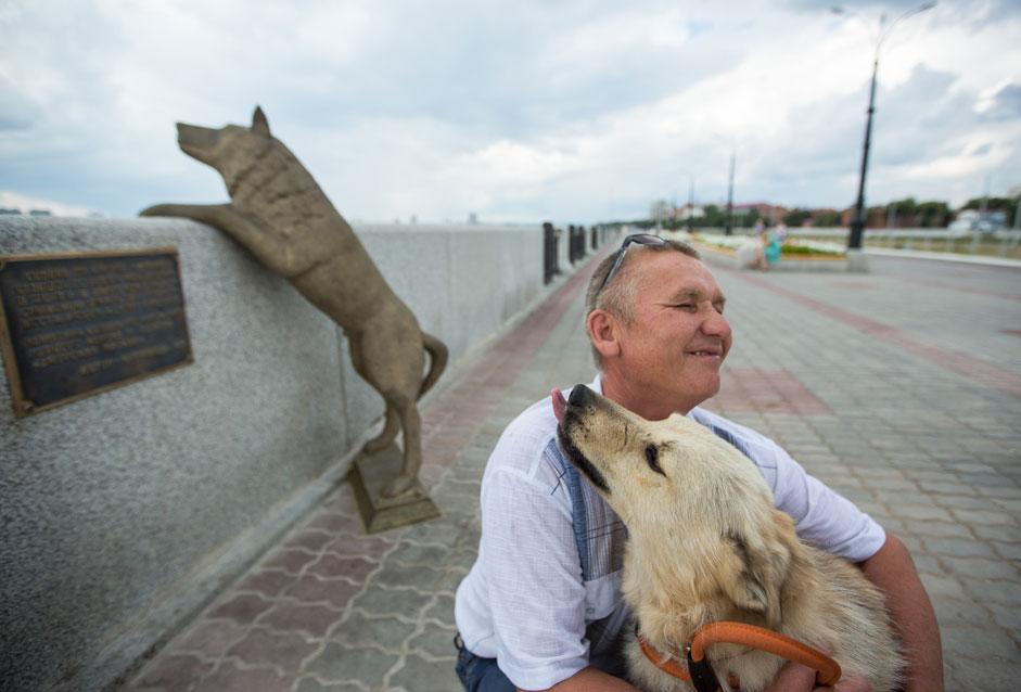 アムール州ブラゴベシチェンスク市。ウラジミール・アンドレーエフさんと愛犬ドルジョーク(親友)が、アムール川堤防上に彫刻家ニコライ・カルナベダさんが制作、建立した記念碑のそばに立つ。2013年の洪水の際、アンドレーエフ家のこの献身的な犬は、首まで水に漬かりながら、ウラジーミロフカ村の家族の家を守った。