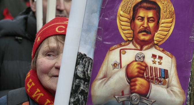 Московјанка со портретот на Јосиф Сталин на комунистичка прослава по повод Денот на заштитникот на татковината на 23 февруари. Извор: AP.