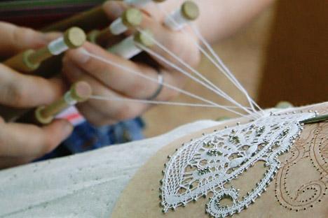 Тантелата се изработува рачно, на специјални перничиња, а се плете со помош на специјални дрвени стапчиња на кои се прицврстува конецот. Извор: Антон Денисов / РИА Новости.
