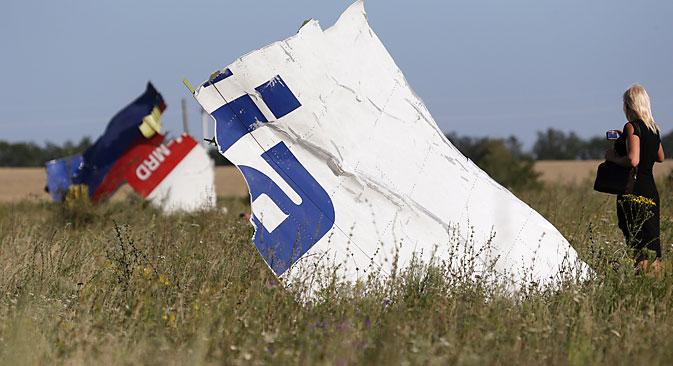Жена фотографира остатоци од паднатиот авион на Малезија Ерлајнс МН17 во близина на селото Грабово, Донецка област