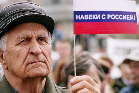 """Украјински пензионер носи руску заставу на којој пише: """"Заувек са Русијом!"""". Извор: PhotoXpress."""