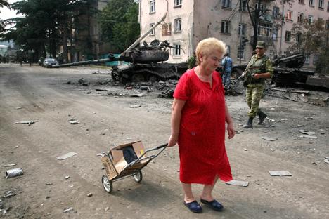 13. август 2008. у ослобођеном Цхинвалију: кућа ове пензионерке је срушена и она нема где да се врати. У позадини: изгорели тенкови грузијске војске и осетински добровољац. Извор: AP.