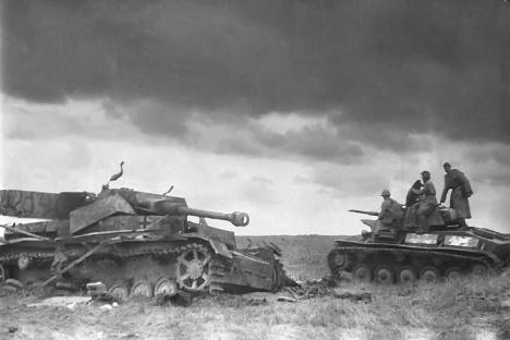 Sovjetski lahki tank T-70 se pelje mimo uničenega nemškega srednjega tanka PzKpfw IV (ali Panzer IV). Bitka pri Kursku je, med drugim, bila tudi največja tankovska bitka druge svetovne vojne. Fotografija iz prostega izbora.
