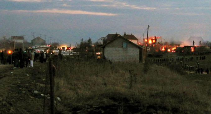 Запаљене куће у селу Чаглавица поред Приштине током албанског иживљавања над Србима 17. марта 2004. У селу је убијено седам особа и више од сто је повређено. Извор: AP.