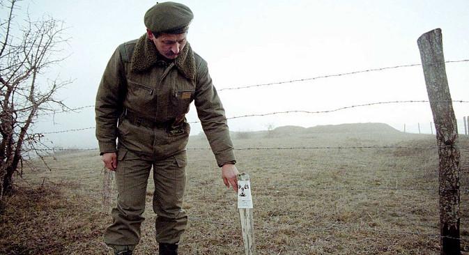 Офицер на Југословенската армија покрај радиоактивно поле во село Рељина кај Прешево, 7 јануари 2001 година. Извор: Ројтерс.