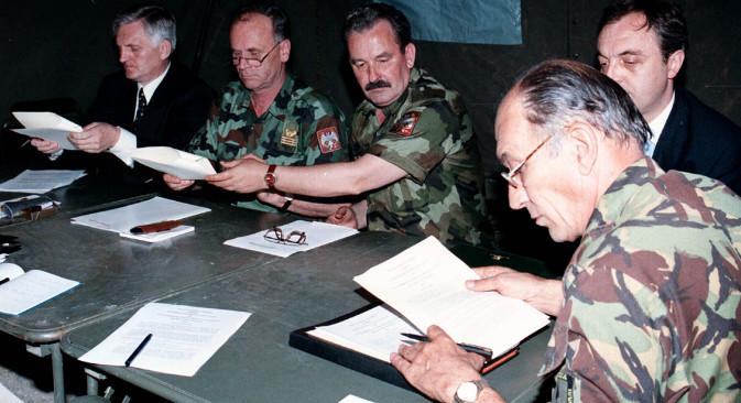 """9. јун 1999. Британски генерал-поручник Мајк Џексон (десно) се спрема да потпише документ који југословенску војску и полицију обавезује да се повуче са Косова (касније назван """"Кумановски споразум""""). ВЈ је започела повлачење 10. јуна. Остали присутни, са десна на лево: портпарол Министарства спољних послова СРЈ Небојша Вујовић, генерал-мајор Благоје Ковачевић, генерал-пуковник Светозар Марјановић. Ваздушне операције НАТО-а заустављене су тек 19. јуна – 10 дана након потписивања Кумановског споразума, а одлуку о њиховом прекиду НАТО је донео још касније – 20. јуна. Извор: Reuters."""
