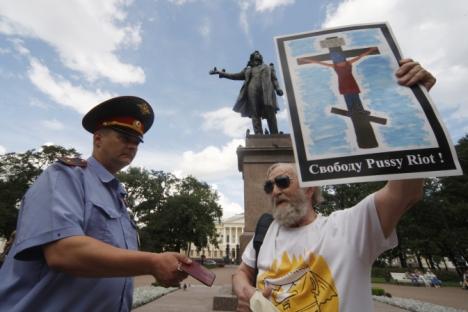 """Полицајац проверава документа учесника митинга подршке осуђеним панкеркама из групе """"Pussy Riot"""" у Санкт Петербургу. На плакату који демонстрант држи учесница групе је приказана разапета на крсту. Извор: РИА """"Новости""""."""