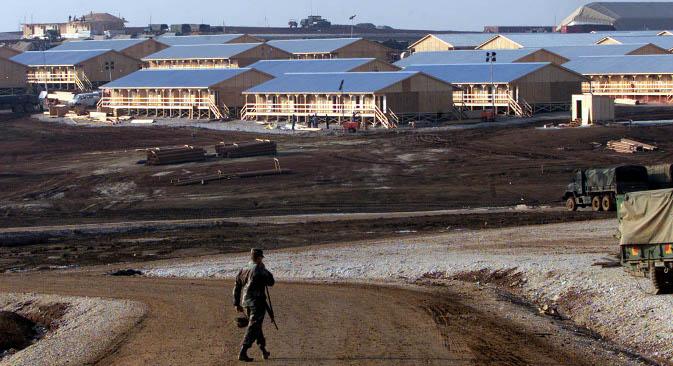 """Амерички војник испред дрвених касарни војне базе """"Бондстил"""" на Косову. База има око 300 објеката и аутономни систем снабдевања електричном енергијом и водом. Извор: Reuters."""