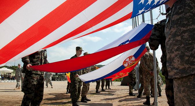 """Војници осам земаља подижу заставе својих земаља на заједничкој војној вежби НАТО-а и """"партнерских"""" земаља одржаној у Слуњу (Хрватска) 26. маја 2012. Македонија и Србија су имале статус посматрача. Вежба је била део програма USEUCOM и њен циљ је био """"постизање интероперабилности Оружаних снага САД, Ратног ваздухопловства САД, Хрватских оружаних снага и партнерских држава"""". Извор: Извор: U.S. Army Europe Images."""