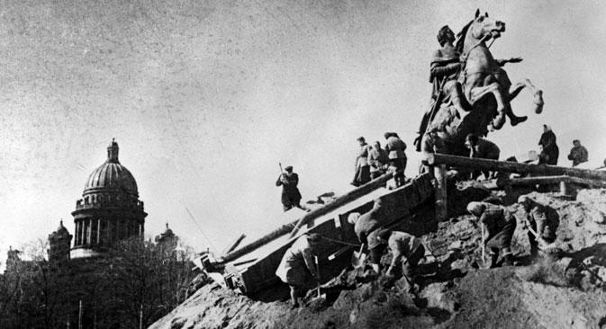 """Током Опсаде Лењинграда упркос глади и хладноћи учињени су херојски напори да се непроцењиво архитектонско и уметничко благо града сачува од немачких бомби. Споменици су стављани у """"оклопе"""", закопавани или преношени, а златне куполе и кровови су премазивани посебном смесом како би били мање уочљиви за немачку авијацију. Извор: РИА """"Новости""""."""