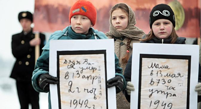 """Млади учесници акције """"Опсадни хлеб Лењинграда"""" држе транспаренте са копијама страница из """"опсадног дневника"""" девојчице Тање Савичеве. Акција је одржана на чувеном Пискарјовском меморијалном гробљу у Санкт Петербургу, на коме је сахрањен велики број жртава Опсаде Лењинграда. Извор: РИА """"Новости""""."""