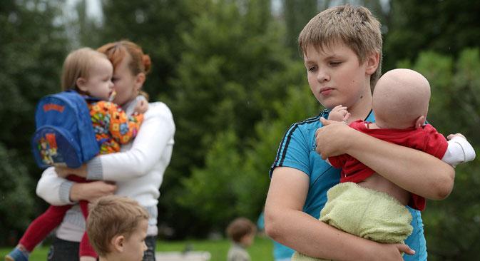 """Избеглице из Славјанска чекају у Доњецку аутобус који ће их пребацити у Русију. Извор: РИА """"Новости""""."""