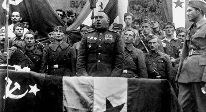 Говор генерала Владимира Ивановича Жданова, чији је 4. гардијски механизовани корпус први ушао у Београд, на митингу поводом ослобођења престонице. Иза њега на трибини стоје официри и војници НОВЈ. Фотографија из слободних извора.