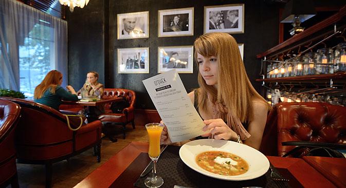 Жена чита специјални мени са храном руске производње у ресторану Огоњок у Јекатеринбургу. Фотографија: Антон Буценко.