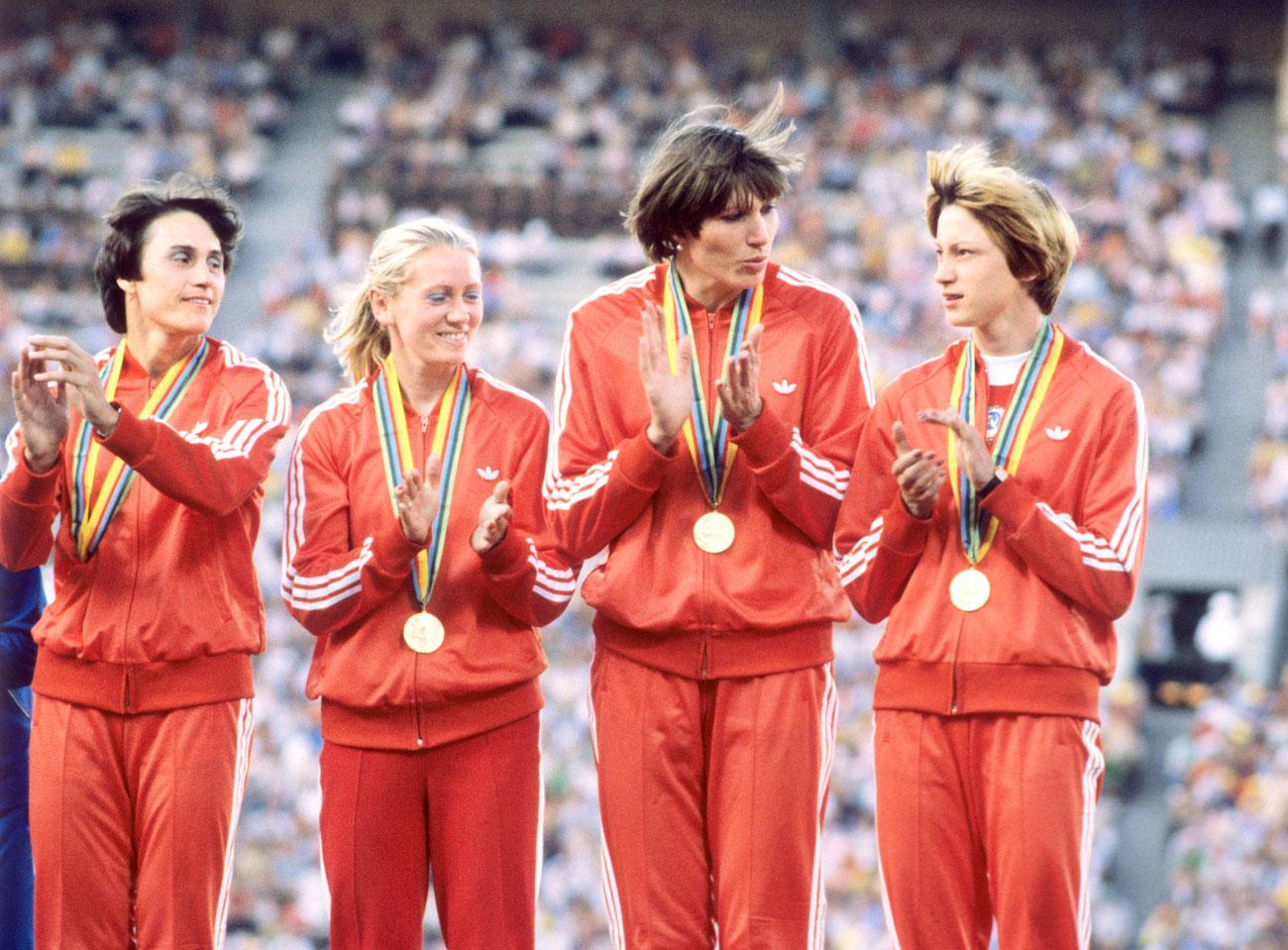 """1980 МОСКВАДо 1980 г. екипите на спортистите се моделират от Общосъюзната къща на моделите в Москва, а до 1988 г. се шият в Армения. Домакинският екип за Олимпиадата през 1980 г. обаче е изключение. За първи път в историята западна компания – """"Адидас"""" (Adidas), създава екипа за съветския отбор. Той се откроява със своята простота, липса на надписи и допълнителни детайли. Официалните костюми на националния отбор е със златист оттенък. На Олимпиадата в Москва през 1980 г. съветските спортисти оглавяват класацията по спечелени медали с 80 златни отличия. Олимпиадата обаче е бойкотирана от спортистите от 65 държави, сред които САЩ, ФРГ, Япония, Турция и Южна Корея."""