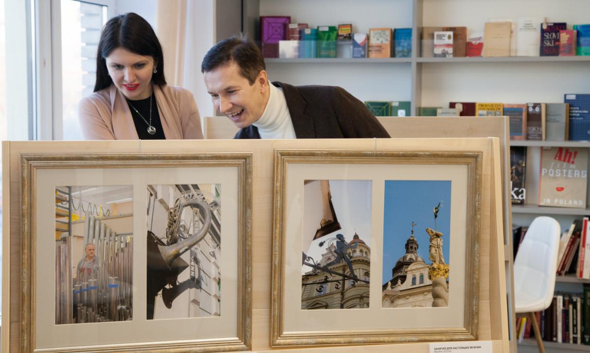 Gosti si ogledujejo razstavljene fotografije.